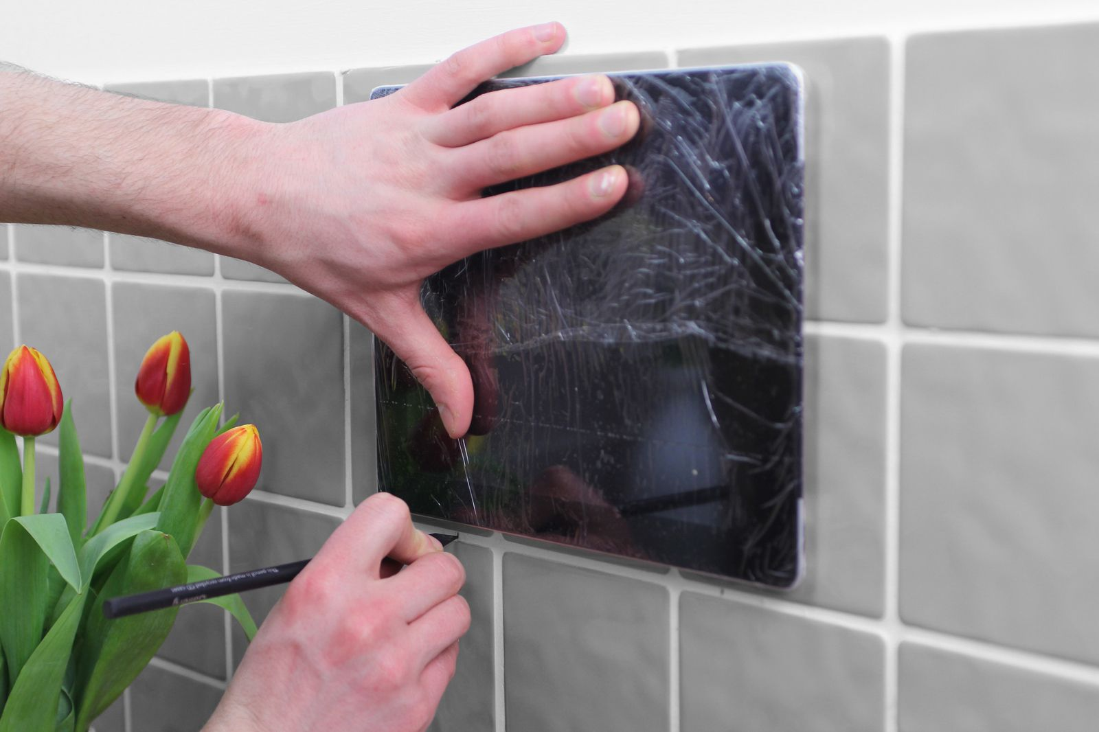 Ipad bathroom wall mount - Ipad Covered In Cling Film Being Held Onto Wall With Positions Being Marked On Wall